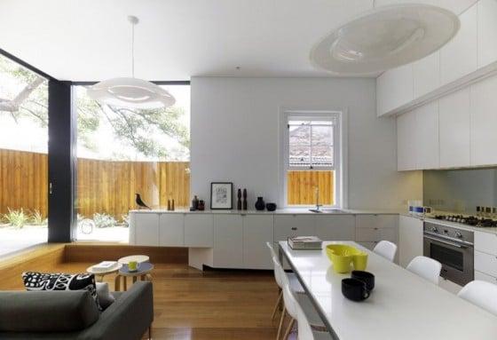 Diseño de cocina con muebles blancos y pisos de madera