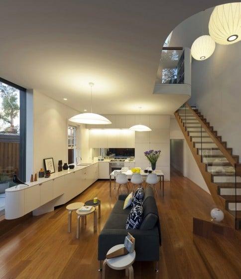 Diseño de cocina moderna junto a escalera de madera