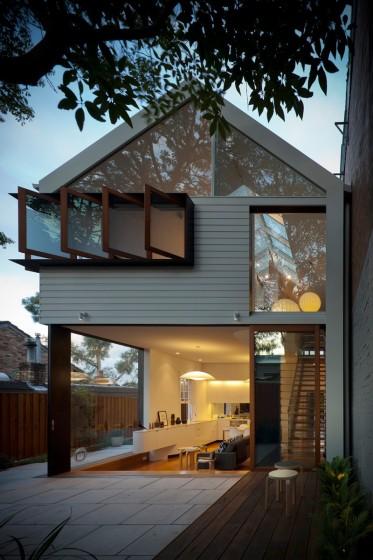 Fachada de pequeña casa de dos pisos con techos a dos aguas