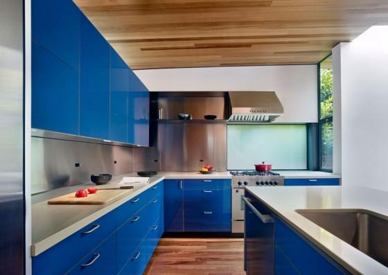 Diseño de cocina con muebles azules y encimeras blancas