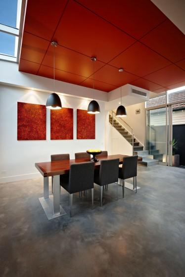 Diseño de comedor moderno con lámparas colgantes y techo rojo