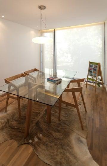 Diseño de comedor sencillo y moderno con sillas de madera y mesa cristal