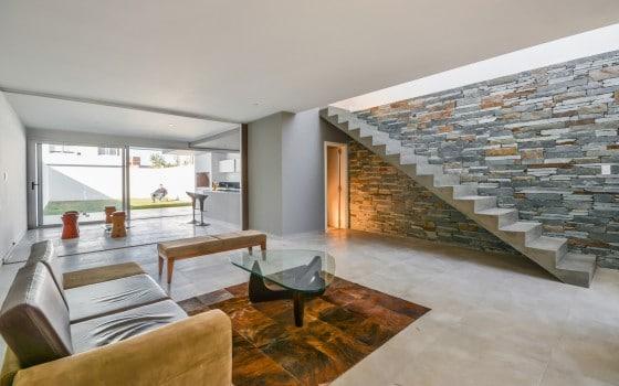 Diseño de interiores de sala sencilla con escaleras de concreto