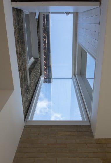 Diseño de tragaluz cubierto de paneles de vidrio en casa rústica