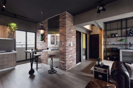 Vista de la cocina con isla de metal y parte del diseño de la sala