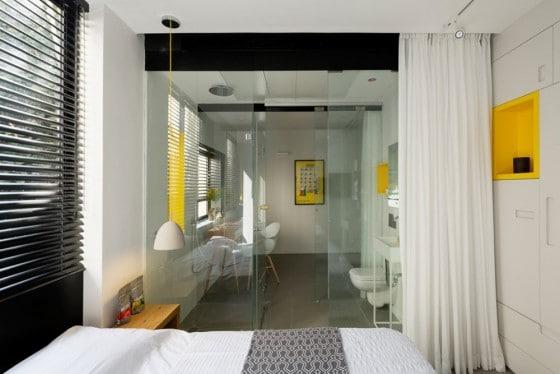 Vista de dormitorio con cuarto de baño paredes de cristal
