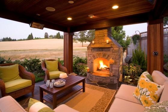 Diseño de terraza elegante con chimenea de piedra y paredes madera