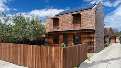Photo of Original casa de dos pisos con fachada de bloques de madera que tienen forma de ladrillo