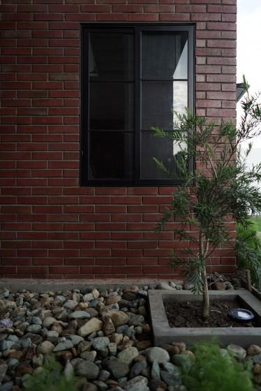 Detalles de jardín con piedras y muro de ladrillos caravista
