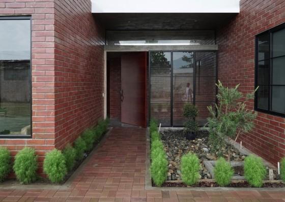 Puerta de ingreso principal a la casa con sendero verde