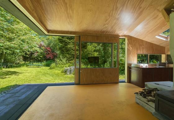 Vista hacia la floresta con ventanas abiertas de pequeña casa