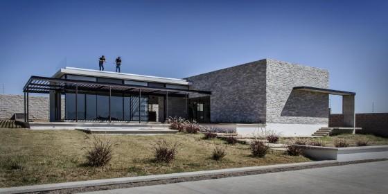 Fachada de casa moderna con piedra y grandes cristales