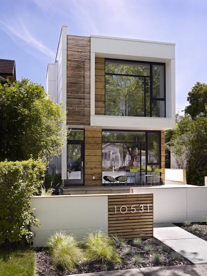 Fachada casa dos plantas con grandes ventanas