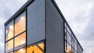 Photo of Diseño casa económica de dos pisos, fachada con paneles de fibrocemento e interiores de madera