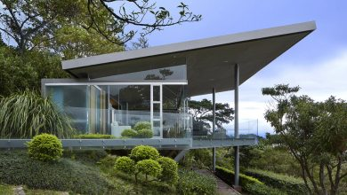 Photo of Diseño de pequeña casa de cristal y acero que se integra al entorno natural
