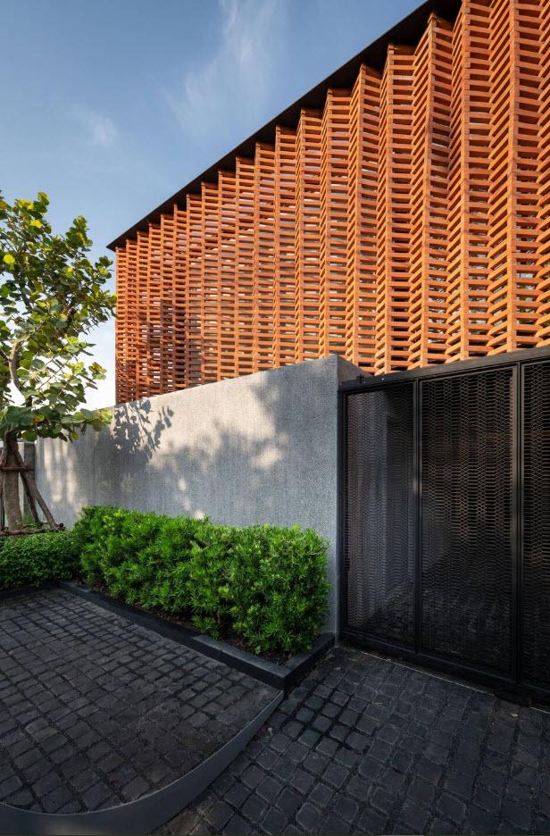 Diseño de celosías de madera en fachada, cerco de concreto y acero de casa
