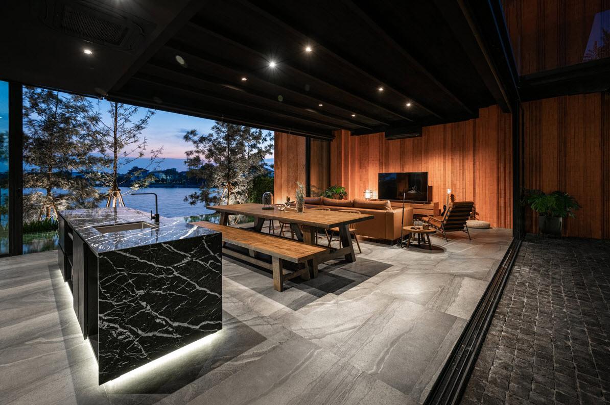 Sala y comedor de casa de campo con vista exterior hacia un lago,