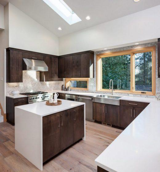 Diseño de cocina iluminado con luz cenital, piaos de madera y encimeras blancas