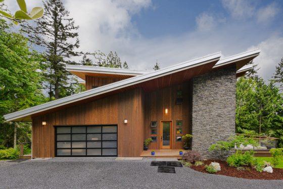 Moderno diseño de casa con techos altos e inclinados, fachada enchapada con madera y piedra