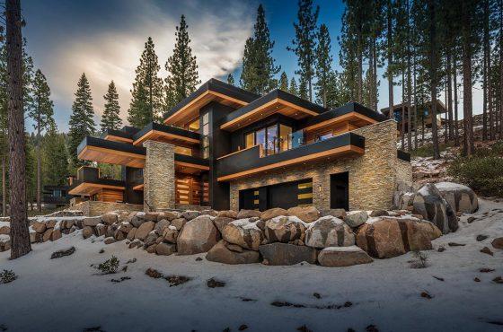 Diseño de casa grande y lujosa con techos planos, destacan la piedra como recubrimiento y detalles de madera y color gris