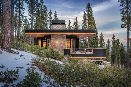 Modern diseño de casa construida en pendiente, techos planos y combinación de piedra y madera