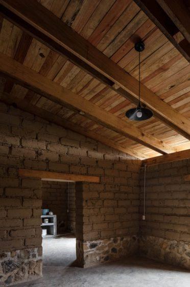Diseño interior de estilo rústico, paredes de arcilla, techo de madera y zócalos de piedra