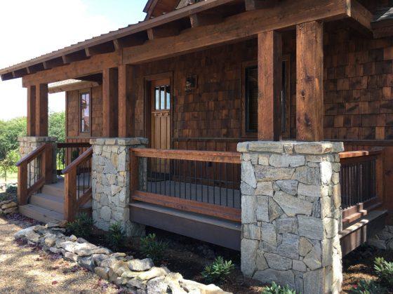 Modelo de casa rústica con pórtico, madera y piedra