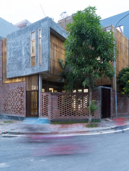 Fachada de casa moderna con texturas rústicas, ladrillo, hormigón y varillas de madera