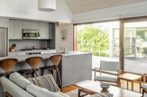 Diseño de sala y cocina con isla, colores blanco y gris claro