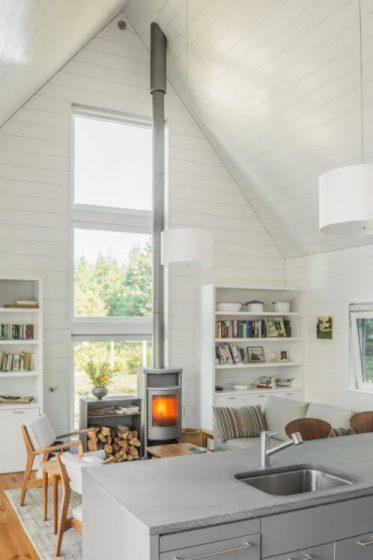 Sala de casa de campo con calefacción por chimenea. techo alto a dos aguas, pintado de color blanco