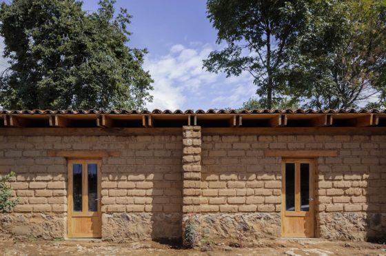 Fachada de casa rústica con paredes de adobe, techo con vigas de madera y tejado
