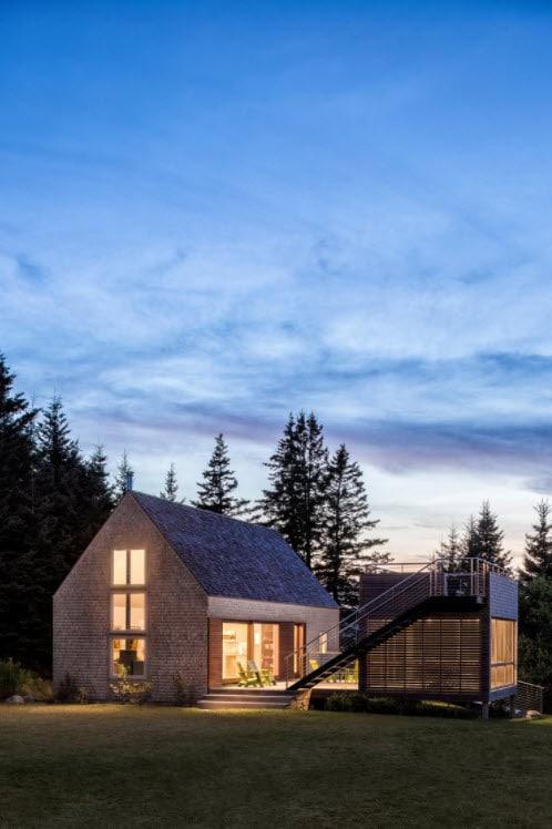 Casa de campo pequeña de madera con mirador hacia el lago, rodeado de pinos