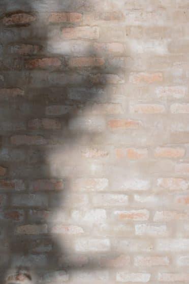 Pared de ladrillo de arcilla cocido con revoque o enlucido difuminado, acabado estilo rústico