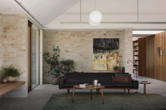 Diseño de sofá de cuero negro y paredes de ladrillo con acabado rústico